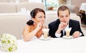 Beautiful young wedding couple drinking cappuccino. — Stock Photo