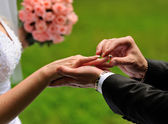 Groom put a ring on finger of his lovely wife. — Stock Photo