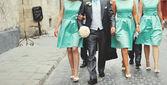 Groom and bridesmaid walking street. — Photo