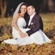 Happy young wedding couple in autumn forest. — Stockfoto