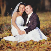 Happy young wedding couple in autumn forest. — Stock Photo