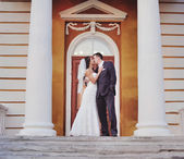 Caucasian wedding couple standing on steps of an old building. — Stock Photo