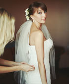 Young bride getting dressed — Stock Photo