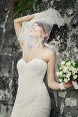 Beautiful bride playing with veil. — Stock Photo