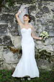 Young bride playing with veil against rock wall. — Stock Photo