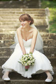 Happy young bride sitting on steps. — Stok fotoğraf