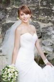 Beautiful bride posing in garden. — Stock Photo