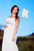 Beautiful young pregnant woman in garden. — Stock Photo