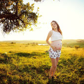 Beautiful young pregnant woman in garden. — Stockfoto