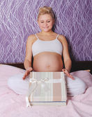 Young pregnant woman sitting on bed — Stock Photo