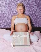 年轻孕妇坐在床上 — 图库照片