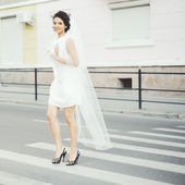 Young brunette bride with veil walking street — Stock Photo