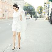 Brunette bride with veil walking street — Stock Photo