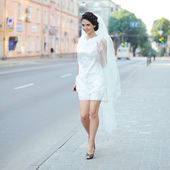 Beautiful bride with veil walking street — Stock Photo