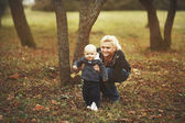 Yong mother with her lovely son in garden — Stock Photo
