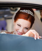Young smiling caucasian bride in white limo. — Stockfoto