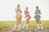 Three funny attractive females wearing dresses, posing in field — Stockfoto