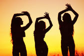 Silhouettes of young women against sunset sky — Stockfoto