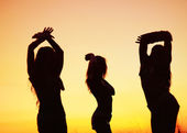 Silhouettes of young women against sunset sky — Stok fotoğraf
