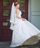 Mooie rode haren bruid poseren met bloemen buiten. europese bruiloft. — Stockfoto
