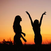 Silhouettes of young women against sunset sky — Stock Photo