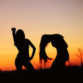Silhouettes of young women against sunset sky — Foto de Stock
