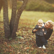 Stock Photo: Being a young mother. Little son and his mom in autumn park.