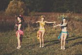Three funny attractive females wearing dresses, dancing in field — Stock Photo