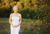 Beautiful pregnant young woman in greek white dress outside — Stock Photo
