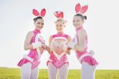 Amusing bunny outside. Three funny attractive females wearing costumes in field — Stock Photo