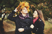 Young sweet couple having date in autumn park. — Stock Photo