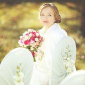 Happy bride with bouquet — Stock Photo