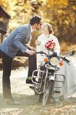 Newlywed couple on motobike — Stock Photo