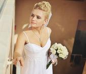 Caucasian bride holding wedding bouquet. — Stock Photo