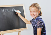 Smiling cute school girl drawing  — Stock Photo