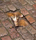 Copper male hand touching female breast. Detail of the pavement in Amster — Stock Photo