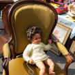 Постер, плакат: Old doll sitting in ocher plush armchair at flea market