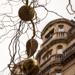 Closeup of branches with gold and silver Christmas balls and fir cone. Building and grey sky on background. Paris at evening. — Stock Photo #17223273