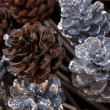 Royalty-Free Stock Photo: Silvered and natural pine cones on stick. Festive Christmas decoration background.