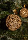 Golden Christmas braided ball on Christmas tree background. — Stock Photo
