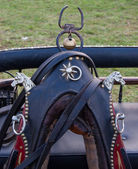 Vintage horse collar decorated with two iron horse heads, rivets and the bell. — Stock Photo