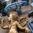 Постер, плакат: Golden baby angel playing on trumpet Colorful bear figurine at background Flea market in Paris