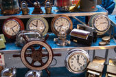 PARIS - JANUARY 13: Old clocks and boat steering wheel for sale at Boulevard de l'Hopital flea market on January 13, 2013 in Paris, France. This flea market serves the professional antique dealers. — Stock Photo