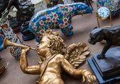 Golden baby angel playing on trumpet. Colorful bear figurine at background. Flea market in Paris. — Stock Photo