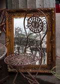 Chairs and mirror in golden frame at flea market in Paris. — Stock Photo
