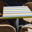 Colorful striped table and four wicker armchairs. Outdoors. — Stock Photo