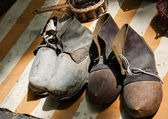 Two pairs of old dirty wooden shoes with leather and shoelaces at flea market. — Stock Photo