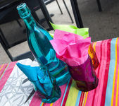 Three colorful glasses, bottle and napkins — Stock Photo
