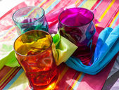 Three colorful glasses and napkins — Stock Photo