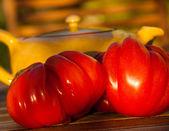 Two shiny ripe beefsteak tomato and yellow ceramic teapot — Stock Photo